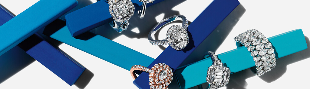 Six different diamond rings with a variety of center stones displayed on blue and teal ring holders