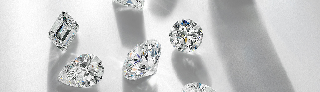 Six loose diamonds of various shapes scattered on a white background