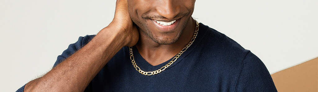 A young man in a dark shirt wearing a gold chain