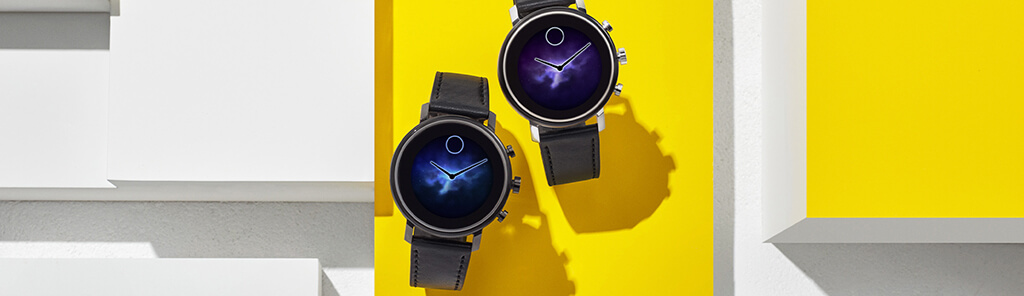 A pair of black watches with digital faces against a yellow background