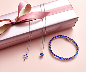 Two different necklaces and bracelet with tanzanite gemstones overlaid on a pink gift box with a pink ribbon