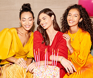 Three young women celebrating a birthday in front of a cake with eight pink candles