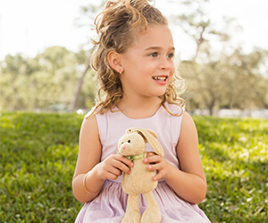 A young girl in a light purple dress holding a brown stuffed bunny