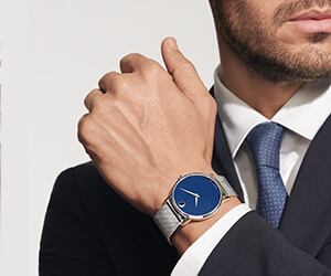 A young man is a dark suit with a blue tie wearing a Movado Men's Museum Classic watch with blue dial