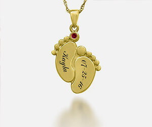 A gold chain with a gold, personalized pendant of a baby's footprints with the name 'Kayla' and the date '07-25-16'