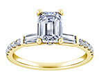 A yellow gold engagement band with numerous diamonds leading to a single emerald cut center stone