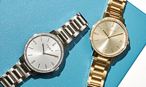 Two analog watches - one silver and one gold - on a blue background