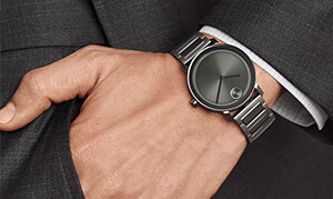 A man's wrist displaying a black on black analog watch