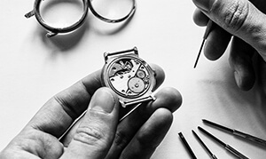 A watchmaker working on the mechanism of a wrist watch