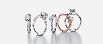 Five different diamond engagement rings set on a gray background