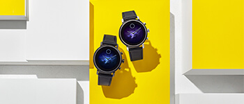 A pair of black watches set against a yellow background