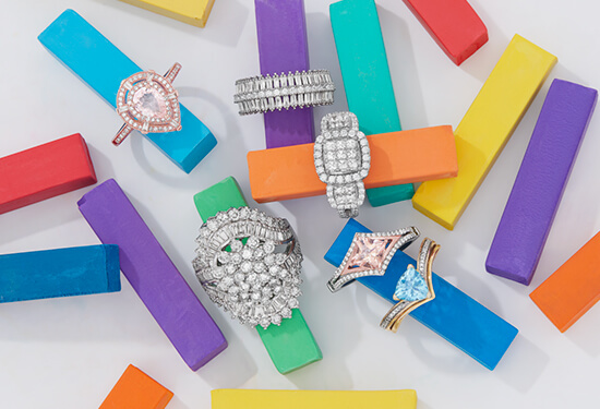 Five different engagement rings displayed on colorful ring stands