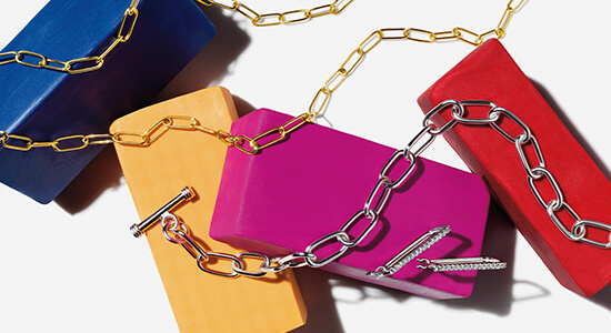 A gold chain, silver bracelet and silver earrings laid across multi-colored blocks