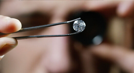 A gemologist inspecting a diamond under a microscope