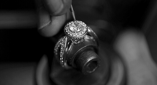 A jeweler working with a fine tool to repair a diamond ring
