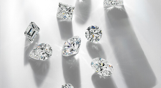 Nine loose diamonds scattered on a white background