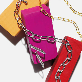 Two chains and a set of earrings set against a multi-colored background