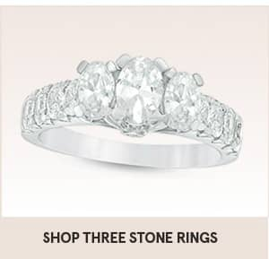 Shop three stone gold engagement rings with the shopping link on this image. The picture shows three main diamonds on ring with other diamonds around the main three diamonds.